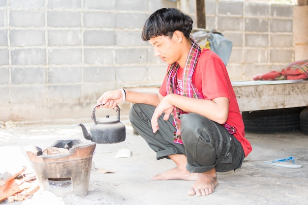 Asian man sitting and cooking on old kitchen
