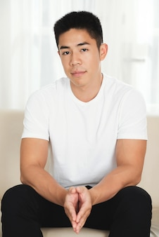 Asian man sitting on couch at home