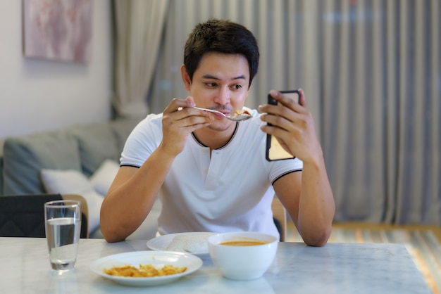 An asian man sitting at the dinner table and had a video call talking to his girlfriend for social distancing dinner together at home.