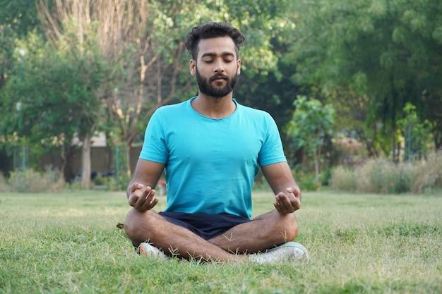 公園で瞑想のポーズで座っているアジア人男性