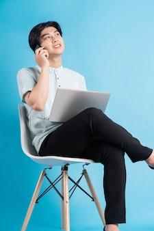 電話をかけながらラップトップを使用しながら椅子に座っているアジア人男性