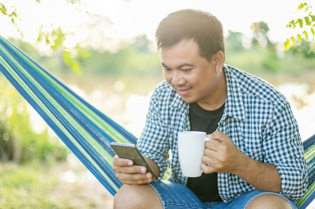 Азиатский мужчина сидит на гамаке и держит чашку кофе и смартфон