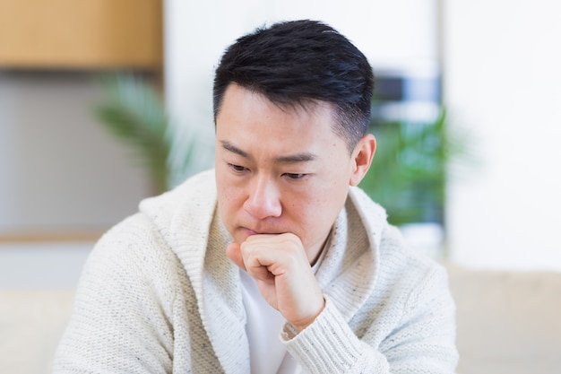 Азиатский мужчина сидит на диване у себя дома задумчивый, обеспокоенный проблемами и депрессией