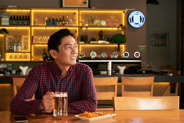 Asian man sitting in pub with mug of beer and snacks and looking at something
