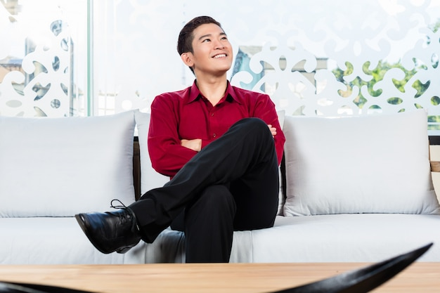 Asian man sitting on sofa in furniture store