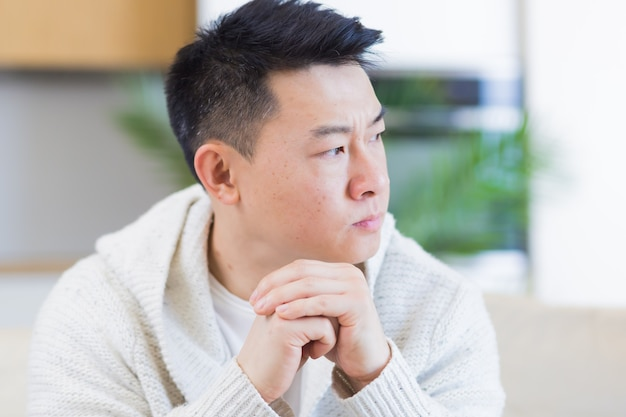 Premium Photo   Asian man sitting on sofa at home pensive worried about  problems and depression