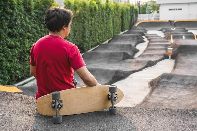 Азиатский мужчина сидит с серфингом или скейтбордом в скейт-парке pumptrack