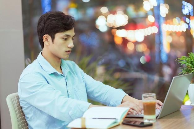 コーヒーショップで一人で働いて座っているアジア人男性