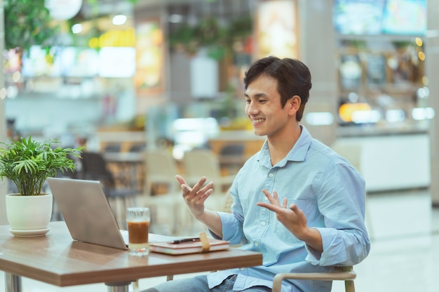 Asian man sitting working alone at a coffee shop