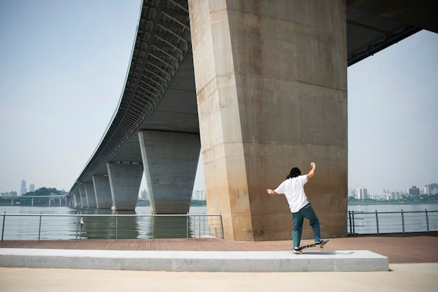 屋外の街でスケートボードをするアジア人男性