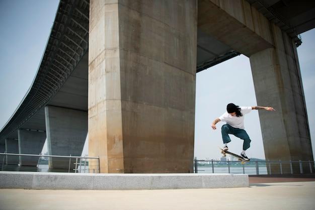 Азиатский мужчина катается на скейтборде в городе на открытом воздухе