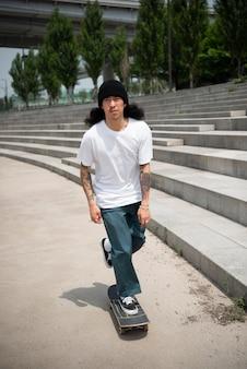 Азиатский мужчина катается на скейтборде в городе