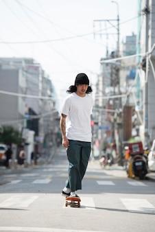 Asian man skateboarding outdoors