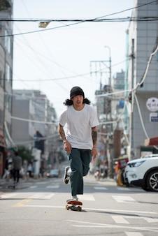 屋外でスケートボードをするアジア人男性