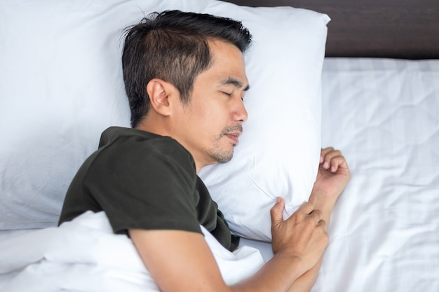 Asian man sleeping comfortably on a white bed