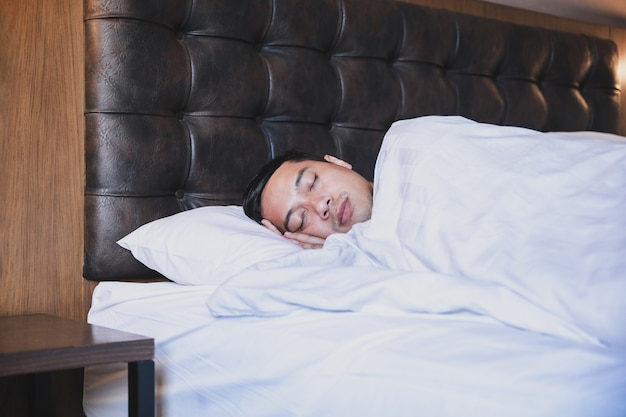 Asian man sleeping tightly on his comfortable bed at home