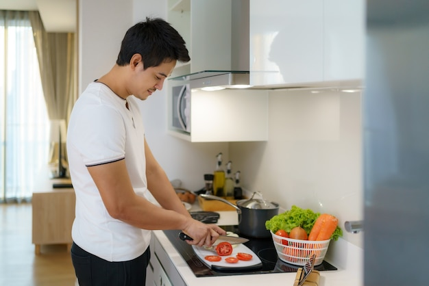 An asian man slices tomatoes on a kitchen counter to prepare for dinner at home.