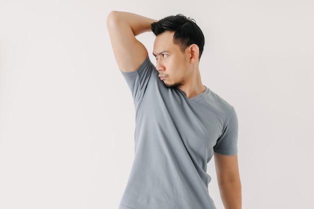 アジア人男性は白で隔離される彼の悪臭の脇の下をかぐ