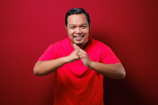 Азиатский мужчина улыбается, глядя в камеру с китайским приветственным жестом, празднует лунный новый год на красном фоне