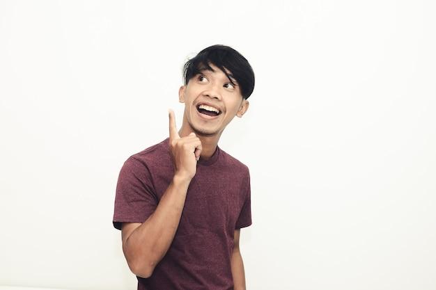 空きスペースを指差しながらカジュアルなtシャツで笑っているアジア人男性
