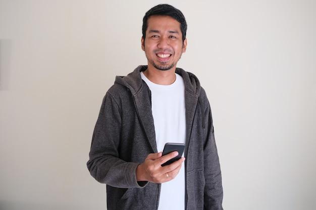 Азиатский мужчина стоит уверенно и улыбается, держа в руке мобильный телефон