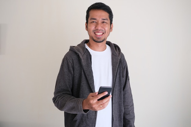 Asian man standing confident and smiling while holding a mobile phone