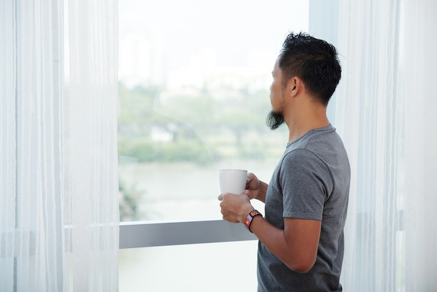 Asian man standing in front of tall window with mug and looking out