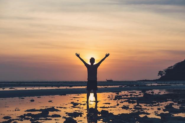 Азиатский человек, стоящий на пляже у моря в утреннем небе с фоном восхода солнца.