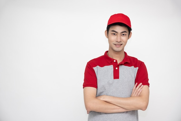 Asian man standing and wearing polo shirt and red hat with crossed arms isolated on white background