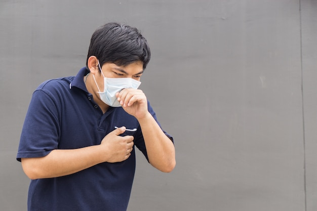 Asian man in the street wearing protective masks, sick man with flu wearing mask.