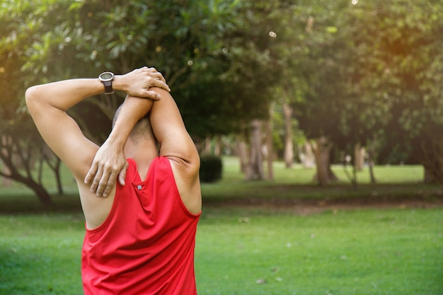 Asian man stretching in the park before running at the morning.