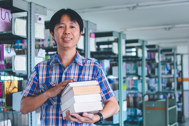 Asian man student hold books in a library