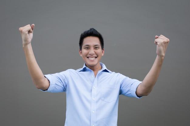空に手を上げてアジア人男性の成功の概念