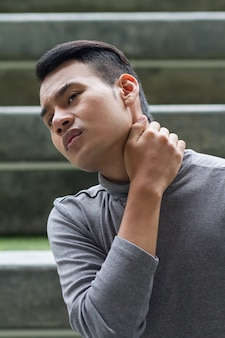 Asian man suffering from neck pain, arthritis, gout symptoms
