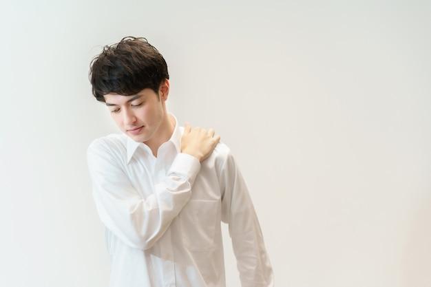 Азиатский мужчина страдает жесткими плечами