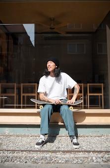 スケートボードから休憩しているアジア人男性