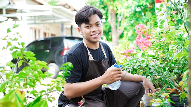 Азиатский мужчина заботится о поливе цветов в домашнем саду