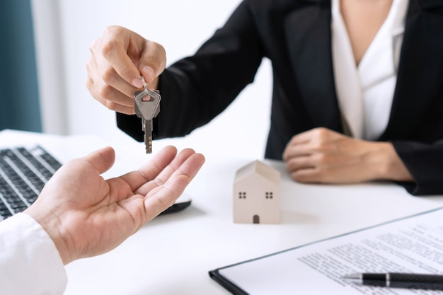 Asian man taking keys from female real estate agent after signing sale purchase agreement. close up