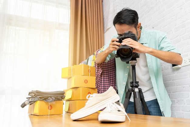 Asian man taking photo to shoes with digital camera for post to selling online