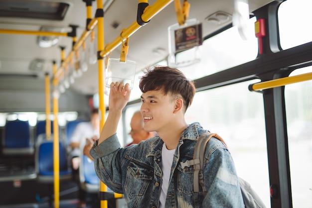 バスの中に立って、公共交通機関を利用しているアジア人男性。