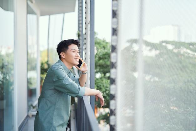 Азиатский мужчина разговаривает по смартфону, улыбаясь громко смеясь, расслабляясь на балконе
