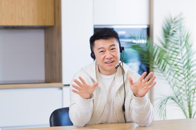 ヘッドセットと自宅の部屋でビデオ通話でオンラインで話しているアジア人男性