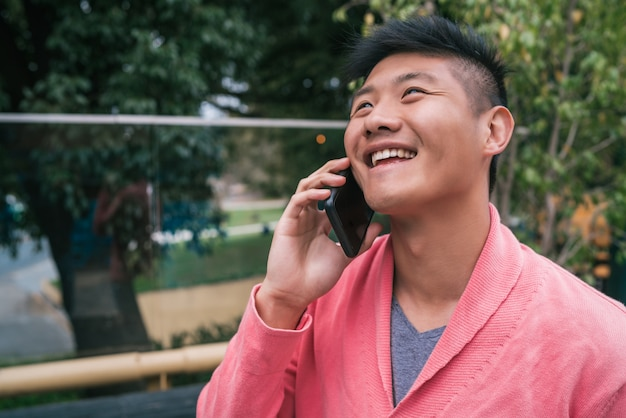 Asian man talking on the phone outdoors.