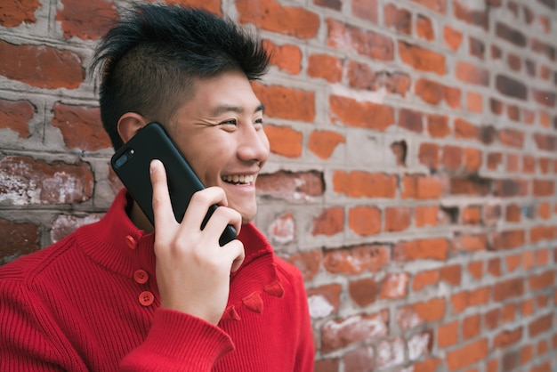 Asian man talking on the phone outdoors