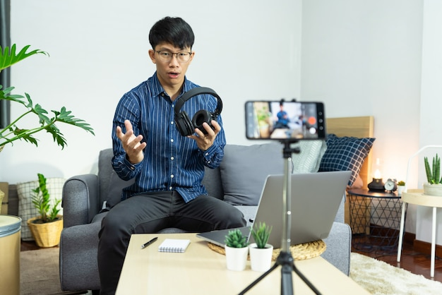 Asian man technology blogger or social media influencer presenting and review on product by smartphone or camera on tripod recording live video