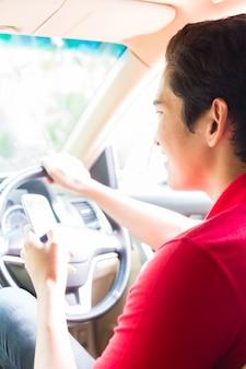 Азиатский мужчина текстовые сообщения во время вождения автомобиля