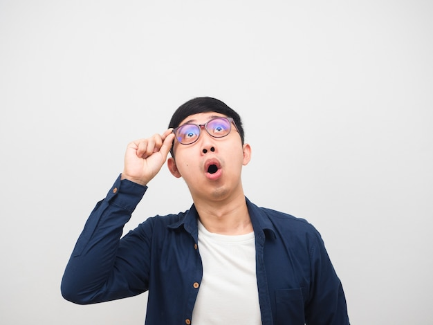 アジア人男性は、コピースペースの白い背景を見上げて驚いた感じで彼の眼鏡に触れます