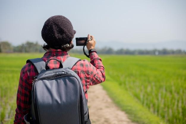 アジア人男性の観光客は、風景と山の写真を撮るためにカメラを使用しています。休日のコンセプトの旅行でリラックスした時間