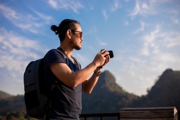 Азиатский турист человек использует камеру для съемки пейзажей и горы. время отдыха на путешествия концепции отдыха