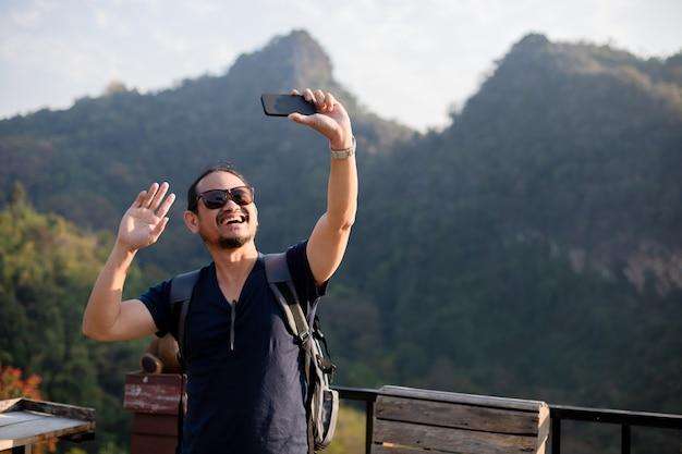 Азиатский человек турист использует мобильный телефон, чтобы сделать селфи для обмена в социальных сетях, через социальные сети.